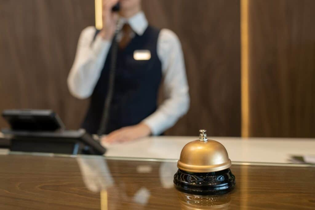 Bell on wooden reception counter against female receptionist consulting clients on the phone