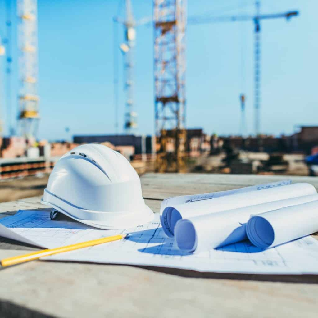 close-up shot of rolls of papers with building plans and hardhat at construction site